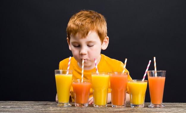 Un beau garçon aux cheveux roux avec des agrumes à partir desquels vous pouvez faire du jus ou d'autres aliments, le garçon est heureux et mange et joue avec les agrumes