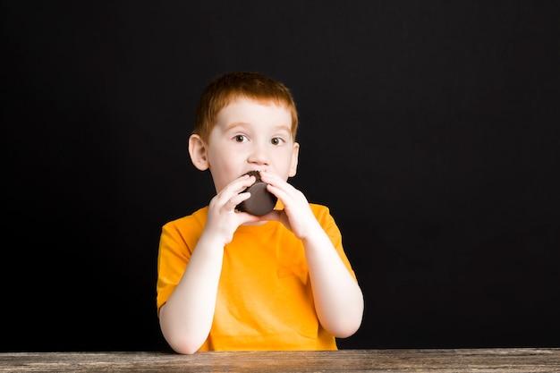 Un beau garçon aux cheveux roux avec un petit gâteau au chocolat, un garçon mange un petit gâteau avec plaisir, une nourriture douce nocive mais délicieuse chez un enfant