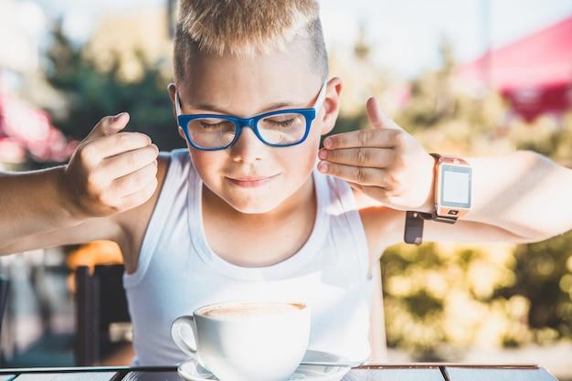 Beau garçon blond dans un t-shirt blanc dans un restaurant buvant du café