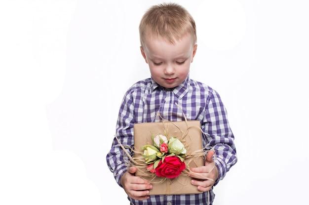 Beau garçon caucasien tenant une boîte avec un cadeau décoré de fleurs. prise de vue en studio sur fond blanc isolé