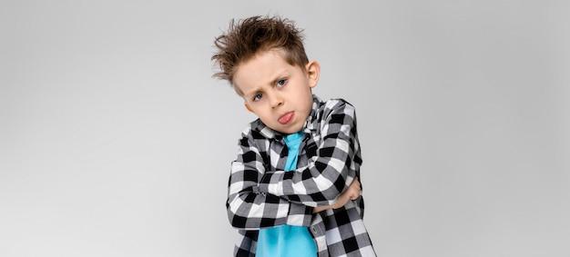 Un beau garçon dans une chemise à carreaux, une chemise bleue et un jean se dresse. le garçon croisa les bras sur sa poitrine. le garçon montre la langue