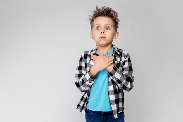 Un beau garçon dans une chemise à carreaux, une chemise bleue et un jean se dresse. le garçon a plié ses paumes sur sa poitrine