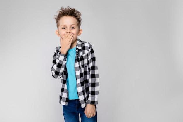 Un beau garçon dans une chemise à carreaux, une chemise bleue et un jean se dresse. le garçon sourit et se couvre la bouche avec la main