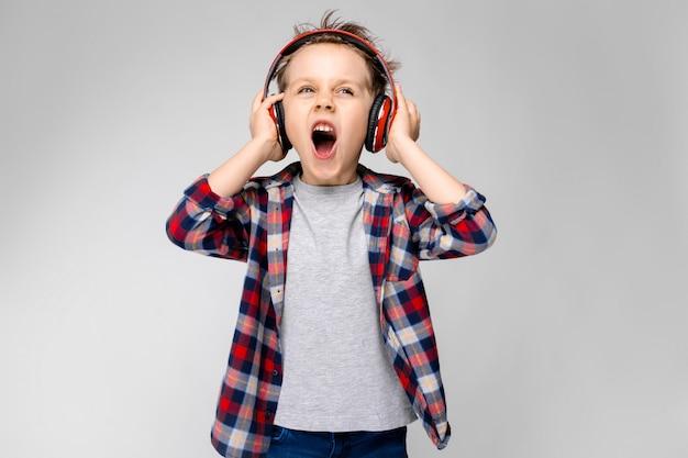Un beau garçon dans une chemise à carreaux, une chemise grise et un jean se dresse sur un fond gris. un garçon au casque rouge chante une chanson.