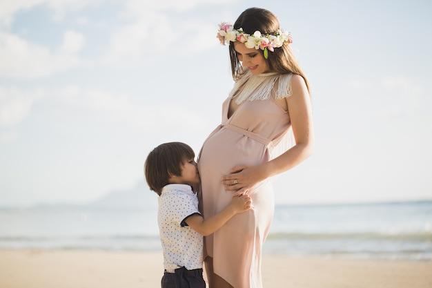 Un beau garçon embrasse le ventre de sa mère enceinte sur l'île.