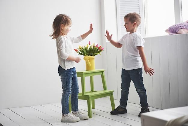 Beau garçon et fille avec des tulipes. fête des mères, 8 mars, joyeux anniversaire