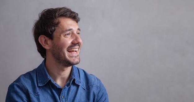 Beau garçon sur fond gris souriant en regardant une caméra.
