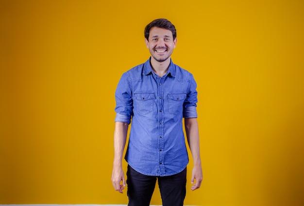 Beau garçon sur fond jaune souriant en regardant une caméra.