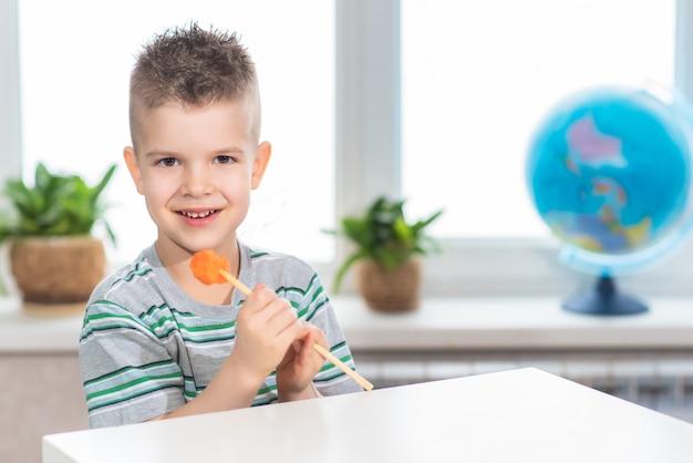Beau garçon mangeant des carottes fraîches sur un bâton à la maison. l'enfant mange des légumes dans sa chambre.