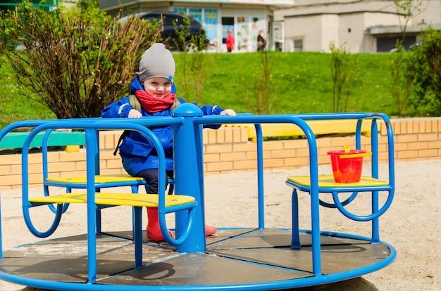 Beau garçon mignon de deux ans dans une veste bleue et une écharpe rouge joue dans une aire de jeux pour enfants lumineuse