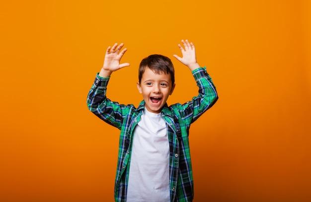 Beau garçon montrant la langue et s'amusant sur fond jaune. garçon émotionnel caucasien.