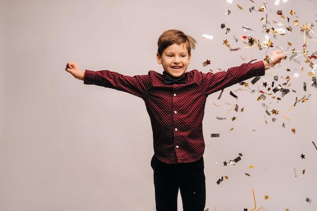 Beau garçon sautant de joie et avec des confettis sur fond gris