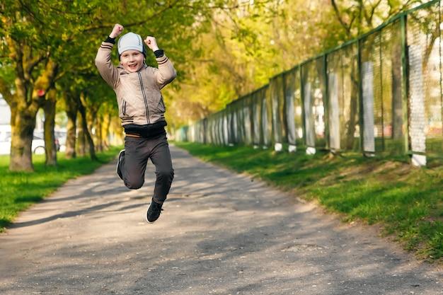 Beau garçon de six ans jouant, sautant, courant, souriant dans le parc.