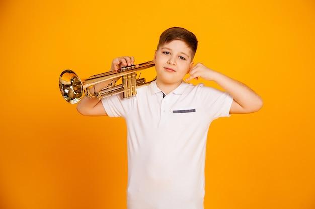 Un beau garçon en t-shirt blanc tient un instrument à tuyaux sur un poêle. le garçon à la pipe montre un geste de la main. appelle moi au téléphone
