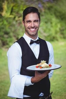 Beau garçon tenant une assiette