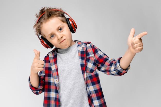 Un beau garçon vêtu d'une chemise à carreaux, d'une chemise grise et d'un jean. un garçon au casque rouge. le garçon pointe avec ses doigts sur le côté.