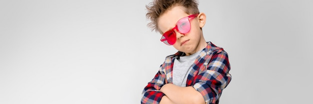 Un beau garçon vêtu d'une chemise à carreaux, d'une chemise grise et d'un jean. un garçon à lunettes de soleil rouges. le garçon croisa les bras sur sa poitrine.