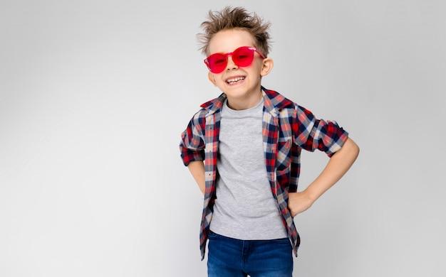 Un beau garçon vêtu d'une chemise à carreaux, d'une chemise grise et d'un jean. un garçon à lunettes de soleil rouges. le garçon a mis ses poings sur ses hanches. le garçon rit.