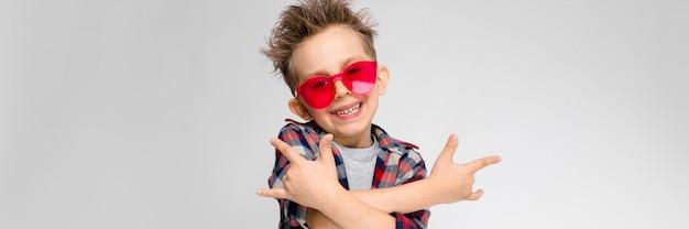Un beau garçon vêtu d'une chemise à carreaux, d'une chemise grise et d'un jean. un garçon à lunettes de soleil rouges. le garçon montre un bouc bascule.