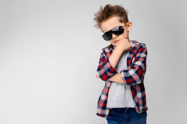 Un beau garçon vêtu d'une chemise à carreaux, d'une chemise grise et d'un jean se dresse sur un mur gris.