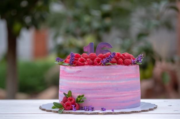 Beau gâteau d'anniversaire avec le numéro seize, décoré de framboises et de fleurs de lavande