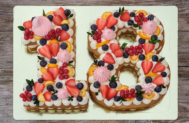 Beau gâteau d'anniversaire sous la forme du nombre dix-huit sur une vue de dessus de fond en bois