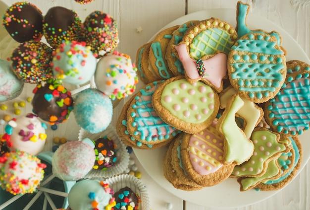 Beau gâteau décoré et biscuits pour pâques sur table