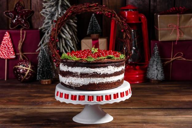 Beau gâteau délicieux avec des baies rouges vives sur la table de noël