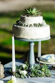 Beau gâteau de mariage blanc avec des fleurs en plein air