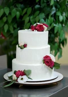 Beau gâteau de mariage blanc avec des fleurs rouges