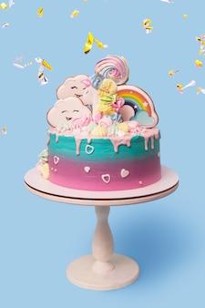 Beau gâteau pour enfants festif avec une licorne sur un support sur un bleu