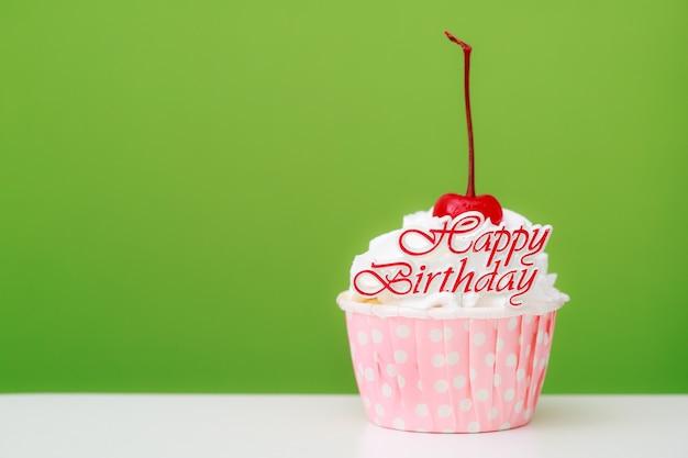 Beau gâteau de tasse avec la cerise rouge sur le dessus et le fond vert