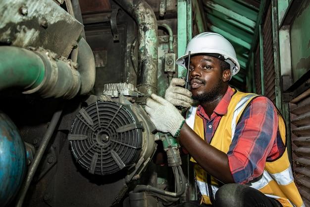 Beau génie industriel afro-américain planifie et discute des moteurs dans les usines de garage de la gare avec walkie takie