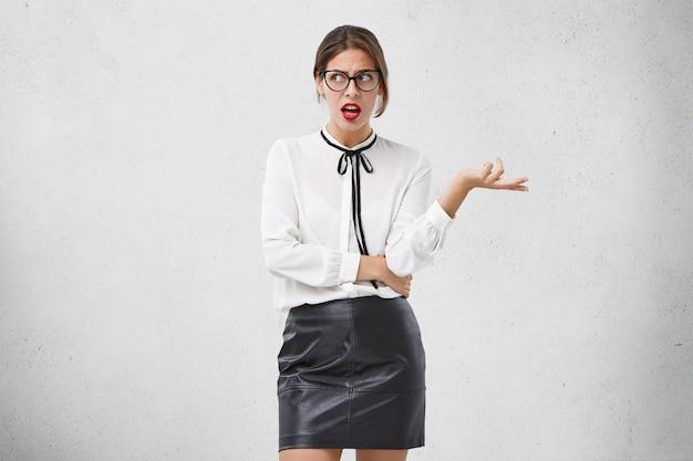 Beau geste féminin confus avec perplexité, essaie de se rassembler avec des pensées, regarde de côté