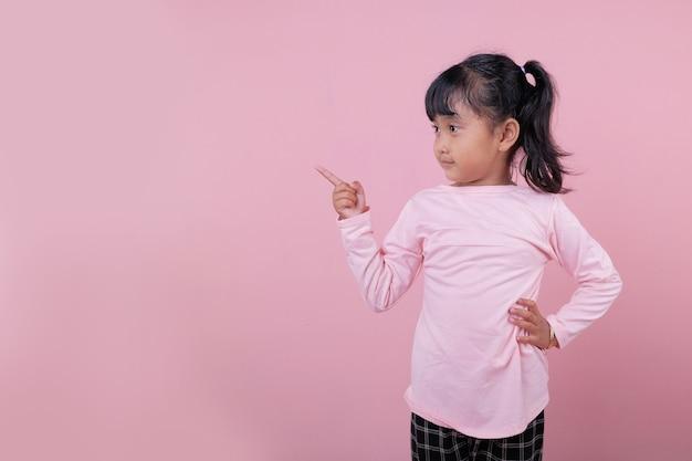 Un beau gosse pointant quelque chose portant un t-shirt rose tendre