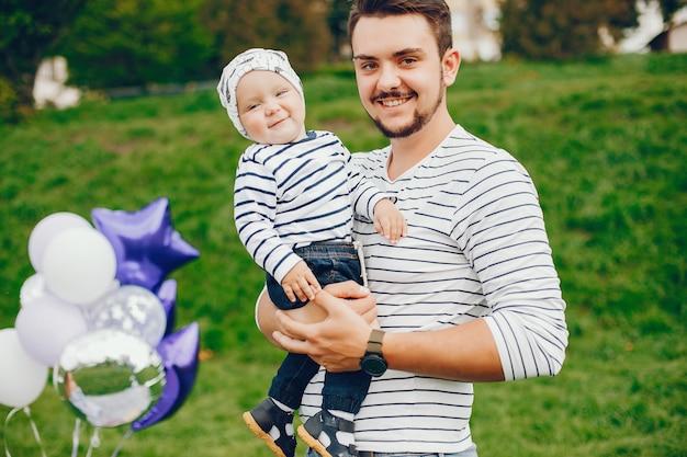 Beau grand et élégant père dans un pull et un jean martèle avec son petit fils doux