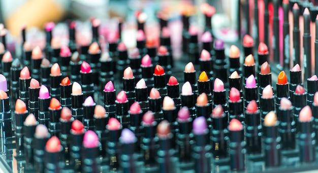Beau grand ensemble de maquillage professionnel multicolore de nombreux rouges à lèvres colorés différents dans des tubes en plastique noir dans une vitrine, photo horizontale
