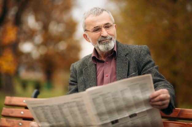 Un beau grand-père avec une belle barbe dans une veste grise est assis sur un banc dans le parc et lit un