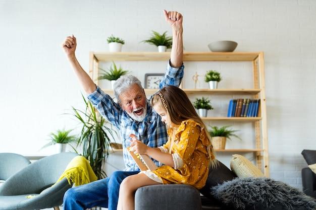 Beau grand-père et petit-enfant parlent et sourient en jouant avec des jouets ensemble à la maison