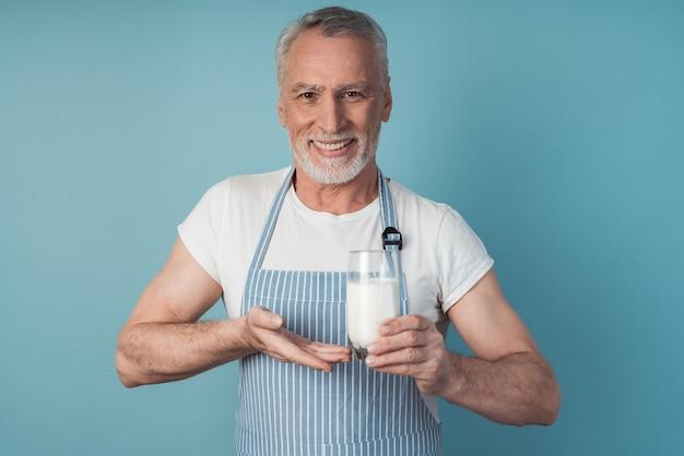 Beau grand-père tenant un verre de lait sur un mur bleu