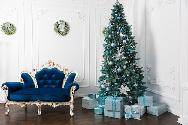 Beau grand sapin de noël avec beaucoup de cadeaux et différentes décorations dans la chambre de style classique avec canapé vintage de style baroque