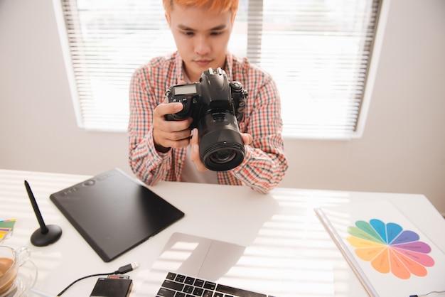 Beau graphiste masculin regardant des photos dans un appareil photo numérique au bureau