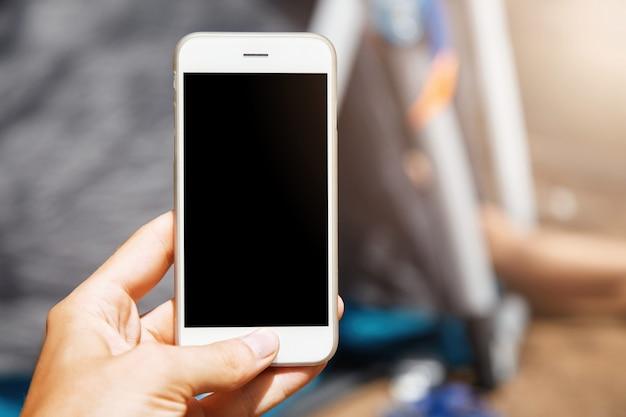 Beau gros plan du smartphone blanc moderne. femme tenant son gadget éteint à jour avec sa main et en appuyant sur le bouton d'accueil.