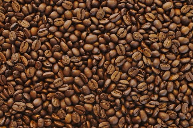 Beau gros plan de grains de café noirs frais bruns