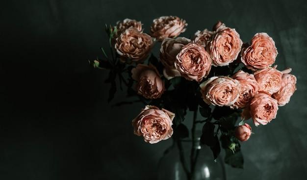 Beau gros plan sélectif tourné de roses de jardin roses dans un vase en verre