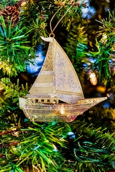 Beau gros plan d'un voilier d'or sur un arbre de noël avec des lumières