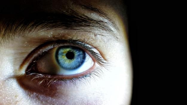 Beau gros plan des yeux bleus profonds d'une femme humaine