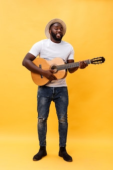 Beau guitariste de style rétro afro-américain jouant de la guitare acoustique isolée sur fond jaune.