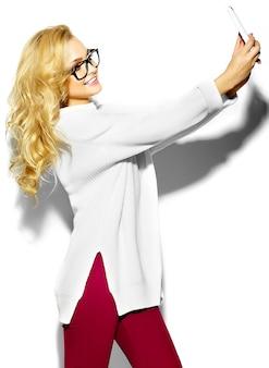 Beau heureux doux mignon souriant femme blonde femme dans des vêtements de chandail blanc chaud hipster décontracté, dans des verres en prenant selfie