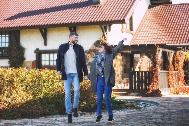 Beau et heureux jeune couple homme et femme dans un beau jardin dans la cour d'une maison de campagne